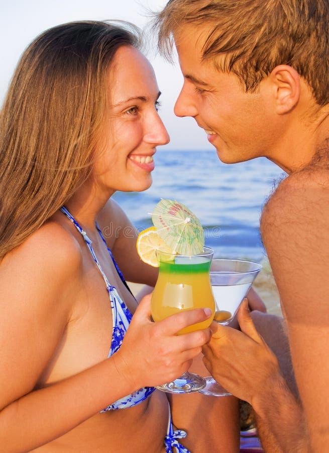 Coppie che bevono i cocktail tropicali sulla spiaggia fotografie stock libere da diritti