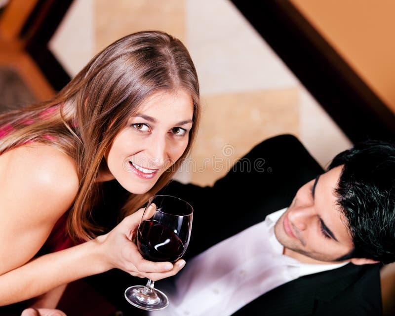 Coppie che bevono i vetri clinking del vino rosso fotografia stock