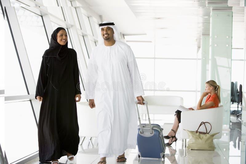 Coppie che camminano attraverso il salotto di partenza dell'aeroporto immagine stock libera da diritti