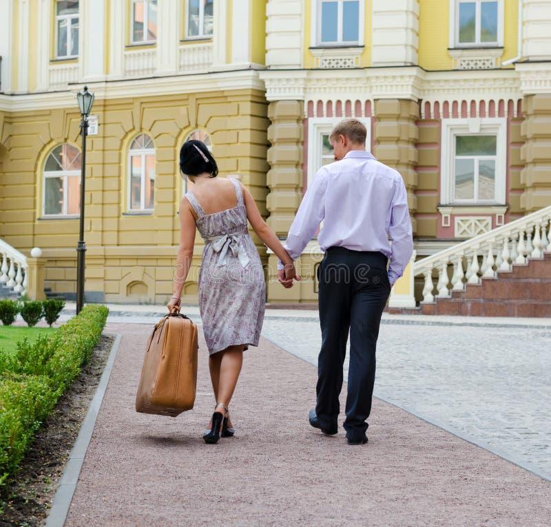 Coppie che camminano con i bagagli di trasporto della donna fotografia stock libera da diritti