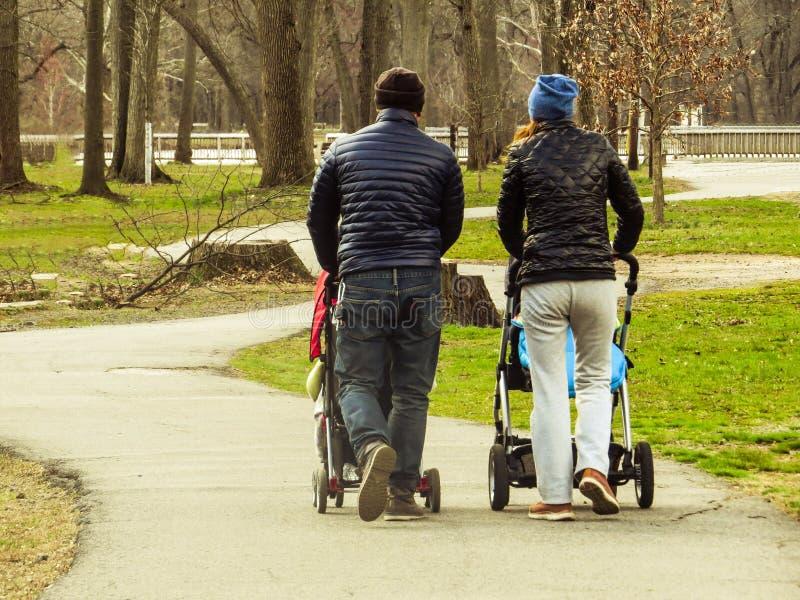 Coppie che camminano con i passeggiatori di bambino tramite un percorso in un parco fotografie stock