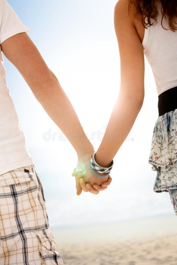 Coppie che camminano congiuntamente sulla spiaggia di estate immagine stock libera da diritti