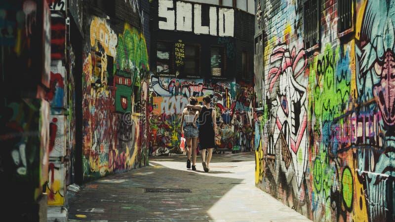 Coppie che camminano giù la via dei graffiti fotografia stock