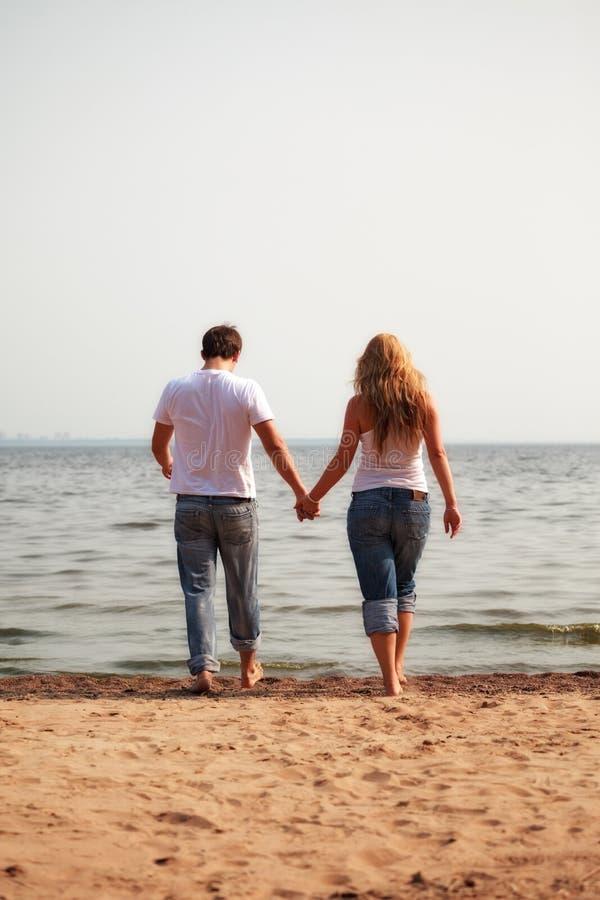 Coppie che camminano su una spiaggia immagini stock