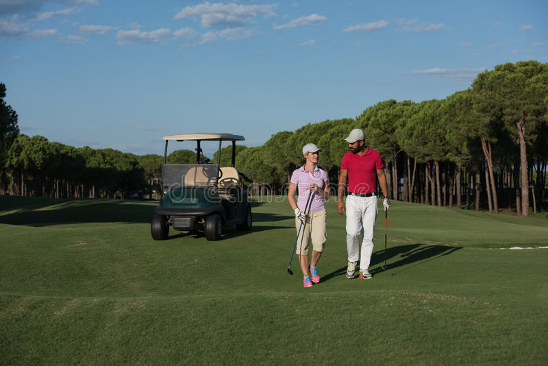 Coppie che camminano sul terreno da golf fotografie stock