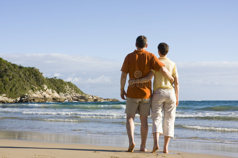Coppie che camminano sulla spiaggia fotografia stock