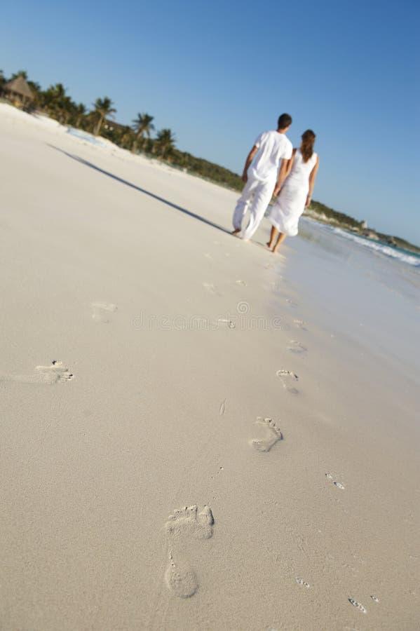 Coppie che camminano sulla spiaggia immagine stock libera da diritti