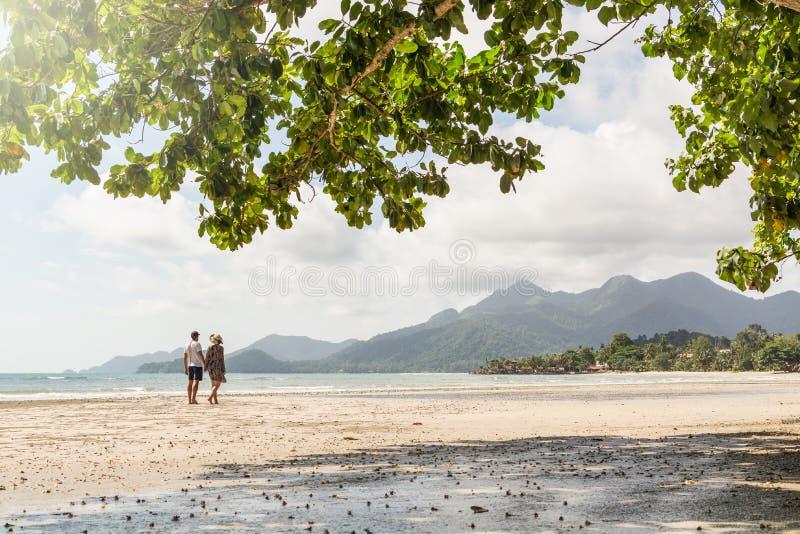 Coppie che camminano sulla spiaggia tropicale sabbiosa sull'isola di Koh Chang, Tailandia fotografia stock libera da diritti