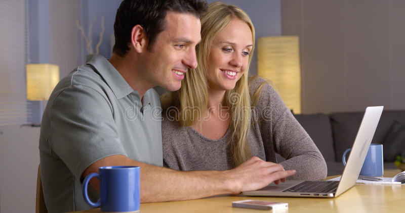 Coppie che cercano le fughe di vacanza sul computer portatile fotografie stock