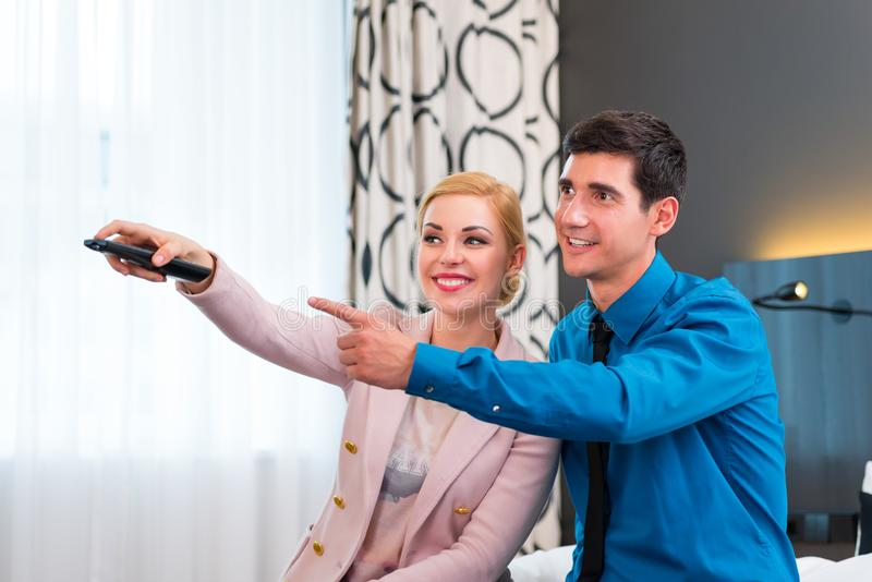 Coppie che commutano TV con telecomando nella camera di albergo immagine stock libera da diritti
