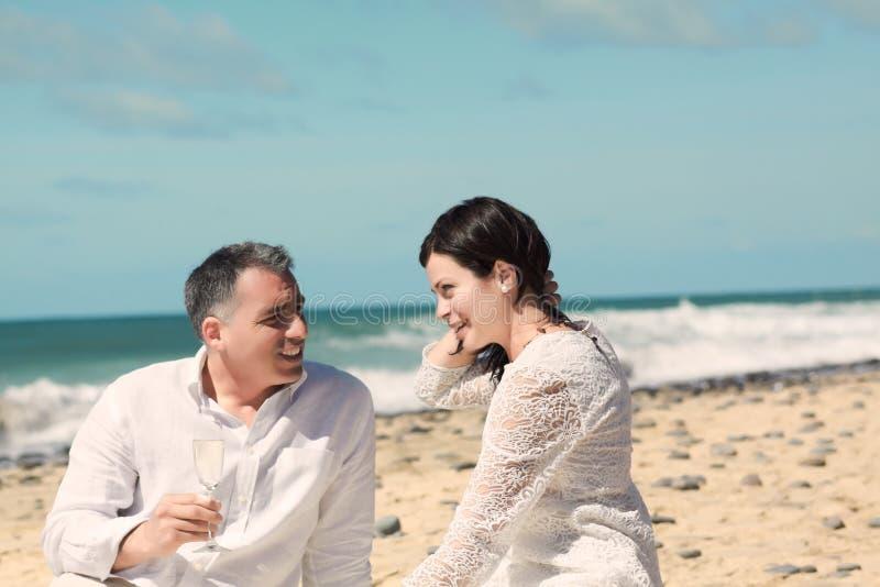 Coppie che comunicano e che si siedono sulla spiaggia immagine stock