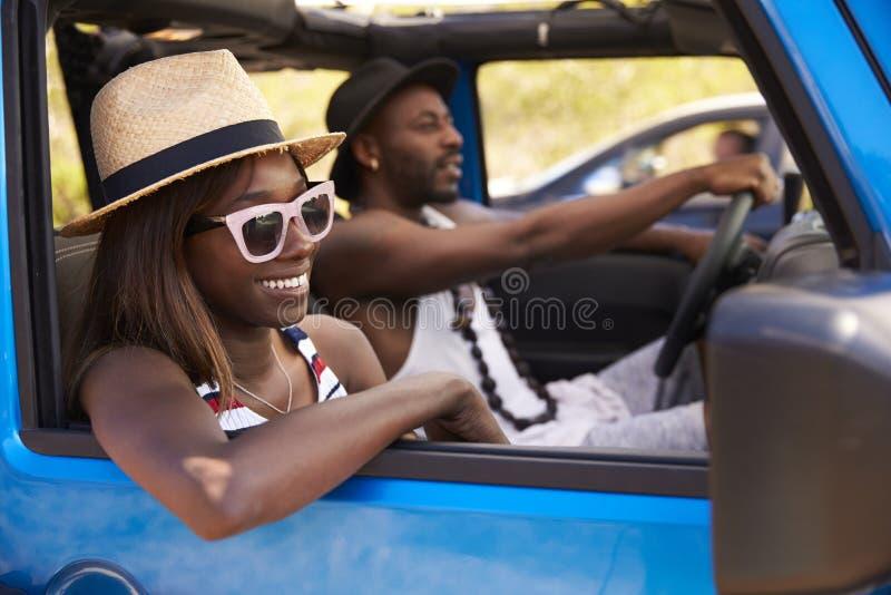 Coppie che conducono automobile senza coperchio sulla strada campestre fotografia stock