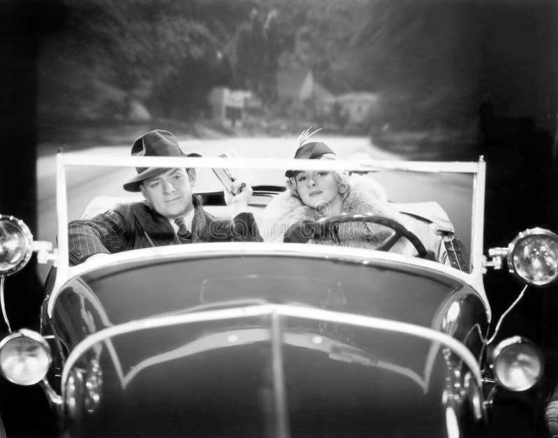 Coppie che conducono un'automobile (tutte le persone rappresentate non sono vivente più lungo e nessuna proprietà esiste Garanzie immagini stock libere da diritti
