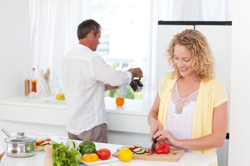 Coppie che cucinano insieme nella loro cucina fotografie stock libere da diritti