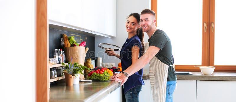 Coppie che cucinano insieme nella loro cucina a casa fotografie stock