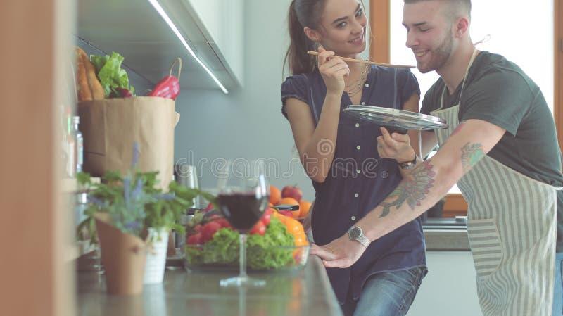 Coppie che cucinano insieme nella loro cucina a casa immagini stock libere da diritti
