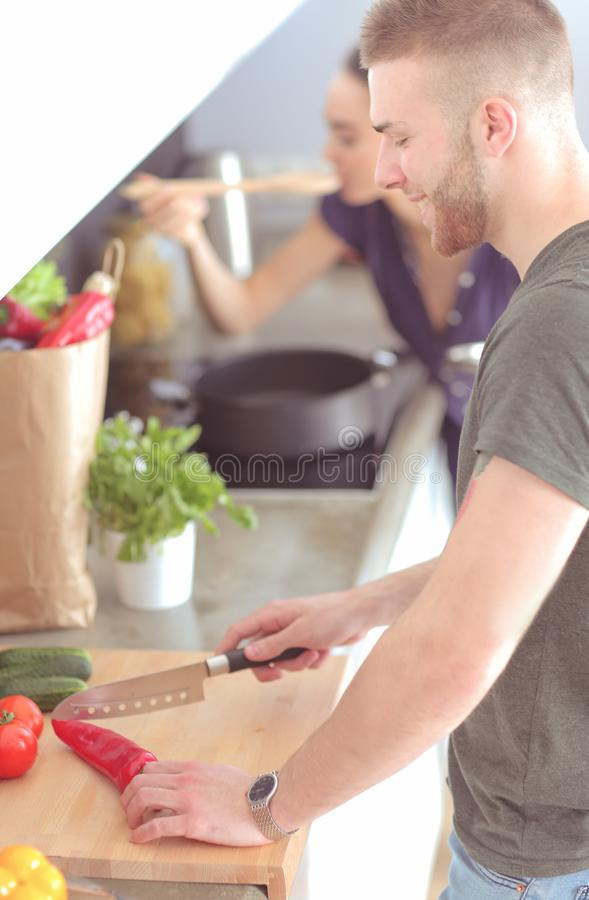 Coppie che cucinano insieme nella loro cucina a casa immagine stock