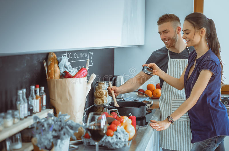 Coppie che cucinano insieme nella loro cucina a casa fotografia stock libera da diritti