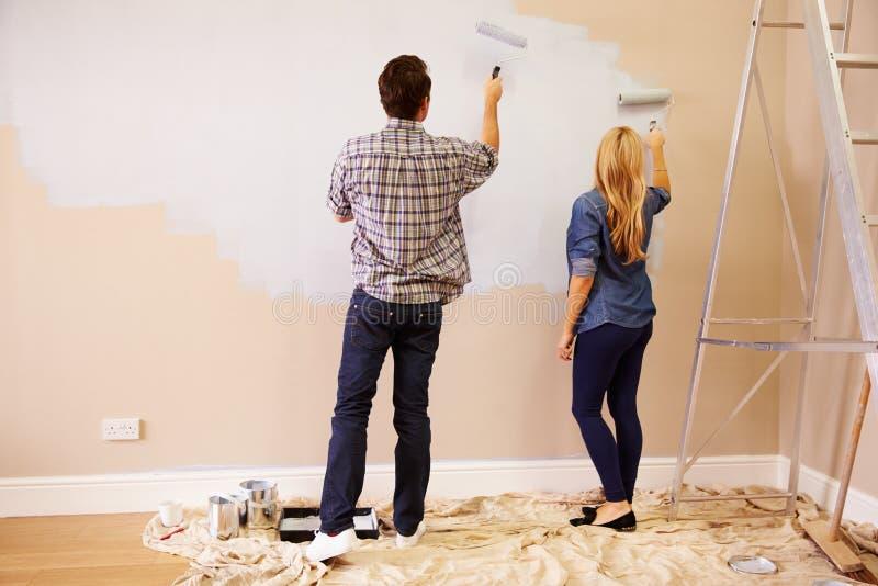 Coppie che decorano stanza facendo uso dei rulli di pittura sulla parete fotografie stock