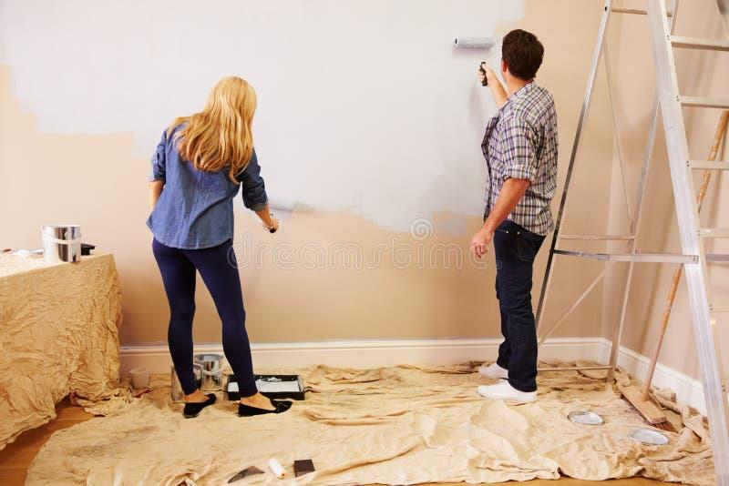 Coppie che decorano stanza facendo uso dei rulli di pittura sulla parete fotografia stock libera da diritti