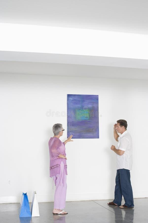 Coppie che discutono sopra la pittura in Art Gallery fotografia stock