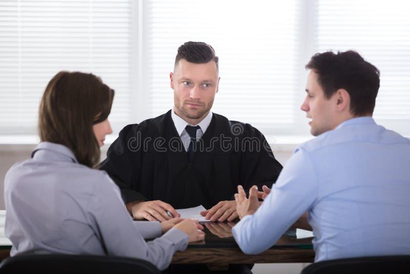 Coppie che discutono a vicenda in Front Of Judge fotografia stock libera da diritti