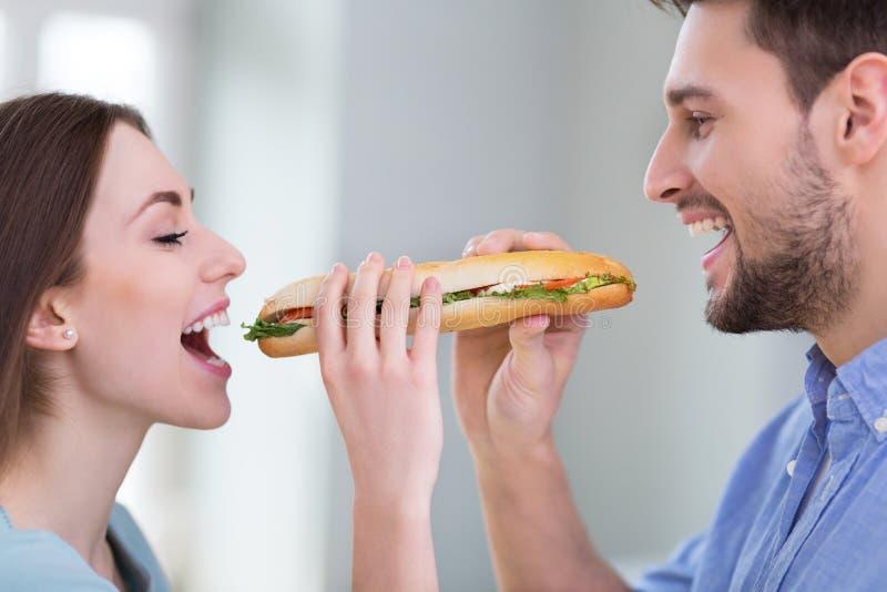 Coppie che dividono panino fotografie stock