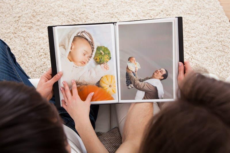 Coppie che esaminano album di foto fotografia stock