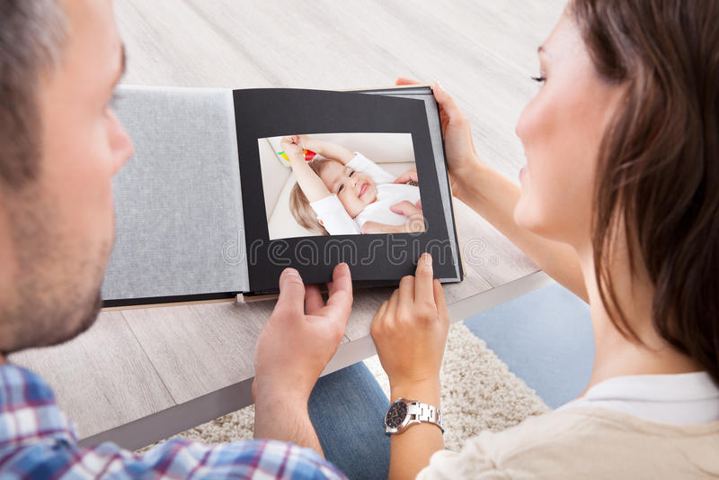 Coppie che esaminano l'album di foto fotografia stock libera da diritti