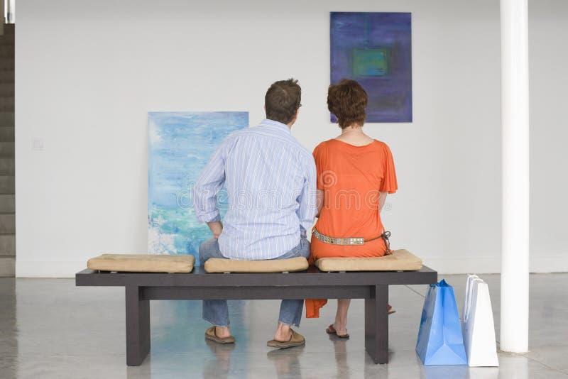 Coppie che esaminano le pitture in Art Gallery fotografie stock libere da diritti
