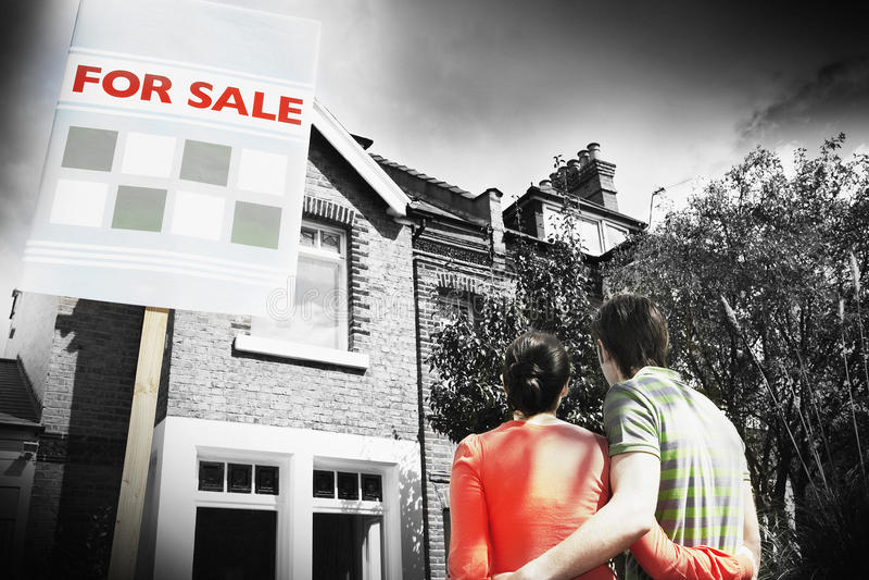 Coppie che esaminano nuova casa con per il segno di vendita immagini stock libere da diritti