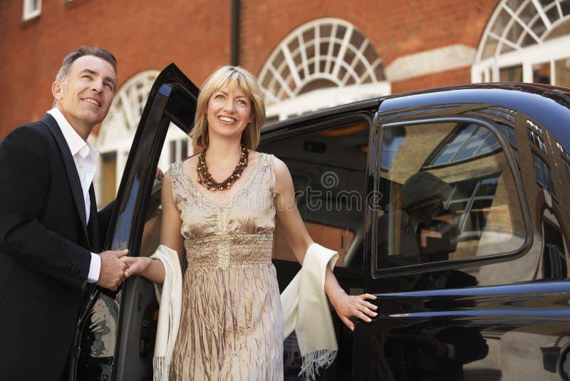 Coppie che escono il taxi di Londra fotografia stock libera da diritti