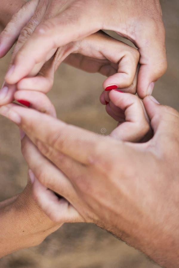 Coppie che fanno forma del cuore delle mani fotografie stock libere da diritti