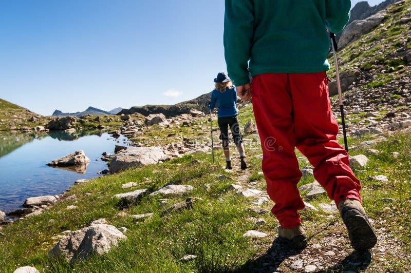 Coppie che fanno un'escursione in montagne fotografia stock
