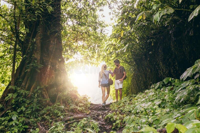 Coppie che fanno un'escursione nella giungla tropicale fotografia stock