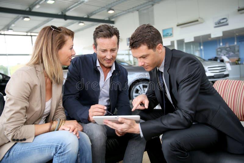 Coppie che fanno una firma digitale sulla compressa in automobile comperare immagine stock libera da diritti