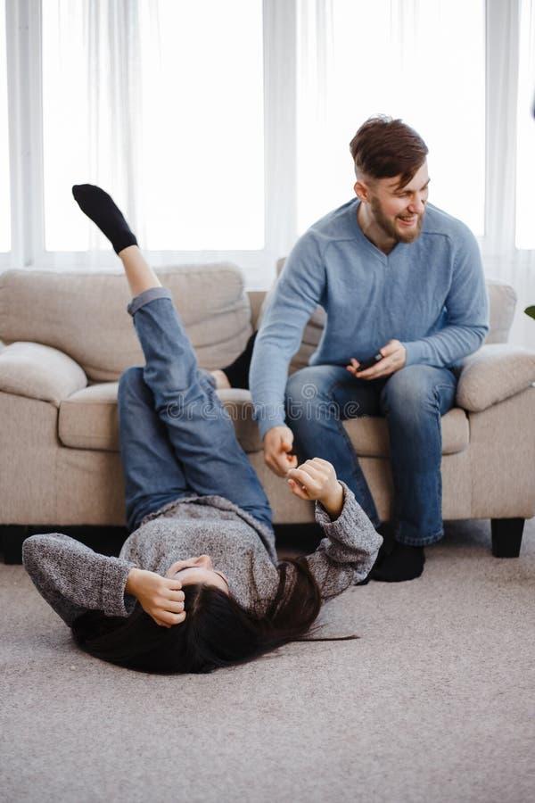 Coppie che flirtano con i telefoni che ridono scherzare immagine stock