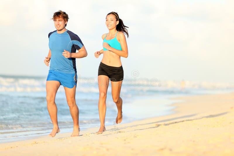 Coppie che funzionano sulla spiaggia immagine stock libera da diritti