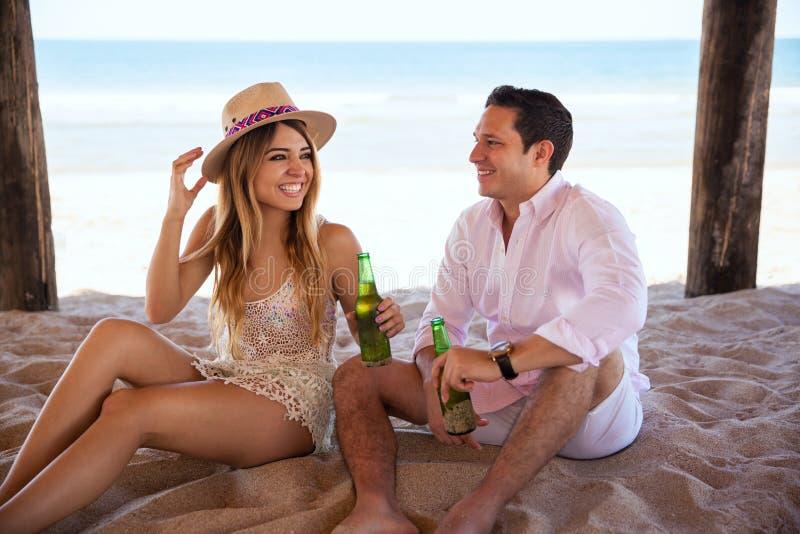Coppie che godono della spiaggia e di una certa birra fotografie stock libere da diritti