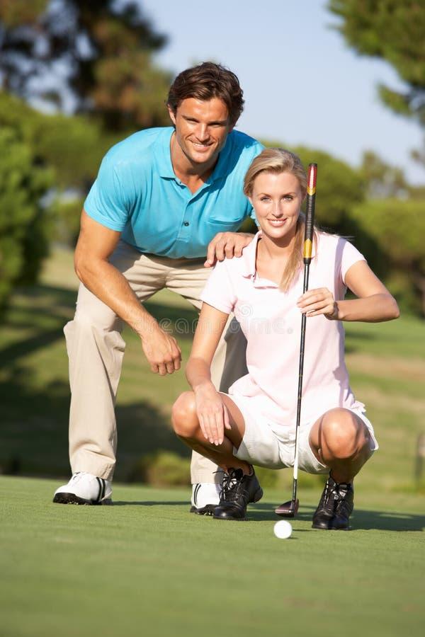 Coppie che Golfing sul terreno da golf immagine stock libera da diritti