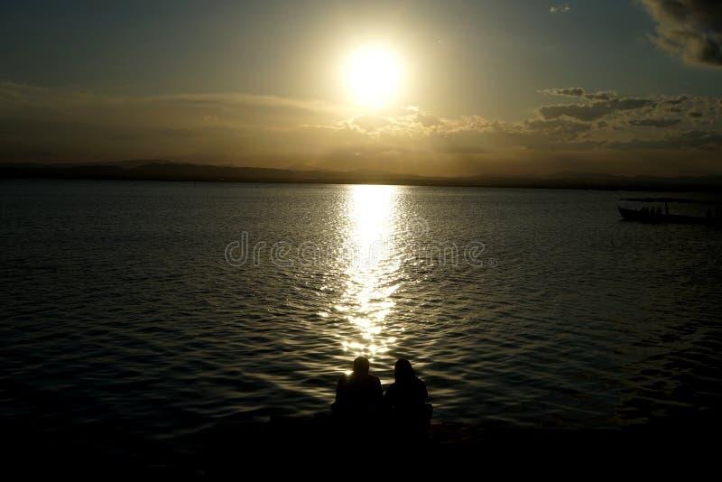 Coppie che guardano il tramonto nel lago fotografie stock
