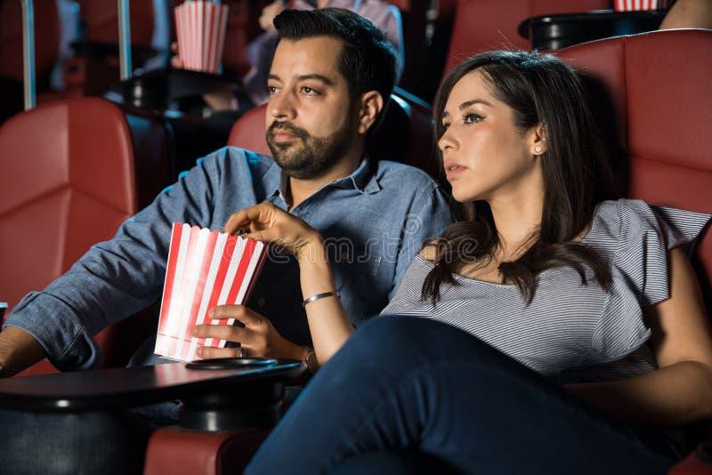 Coppie che guardano un film e che mangiano popcorn fotografia stock