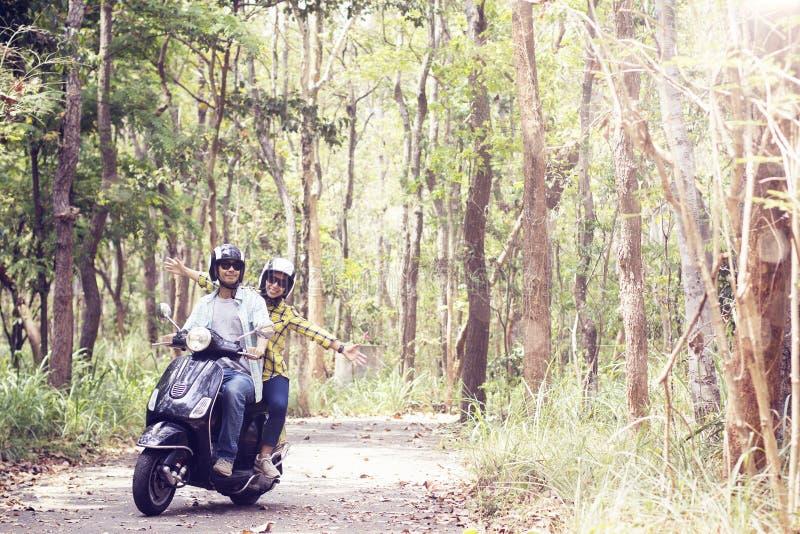 Coppie che guidano il loro motorino attraverso la foresta immagine stock libera da diritti