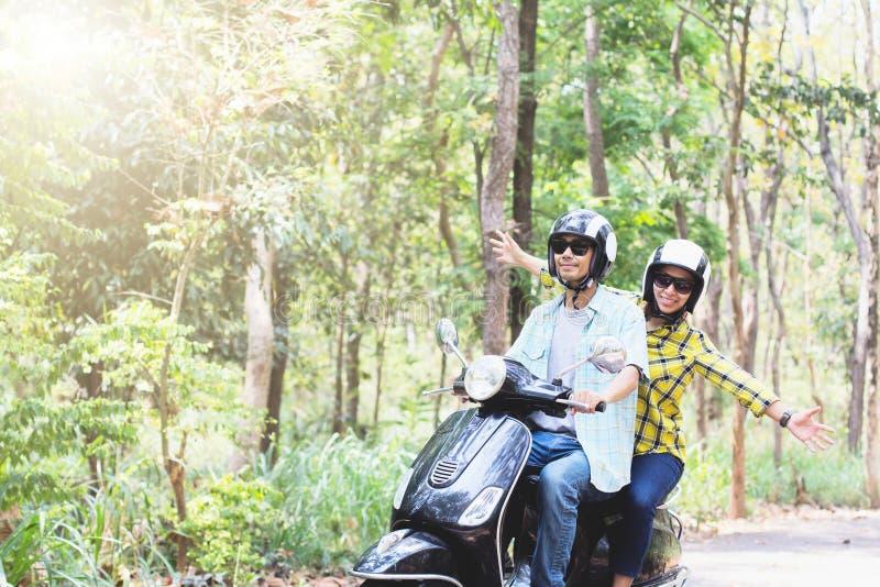 Coppie che guidano il loro motorino attraverso la foresta fotografia stock libera da diritti