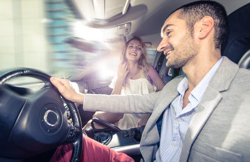 Coppie che guidano velocemente su un'automobile sportiva immagini stock