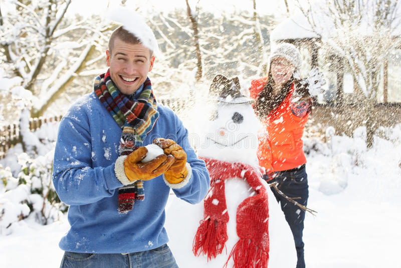 Coppie che hanno lotta della palla di neve in giardino immagini stock libere da diritti
