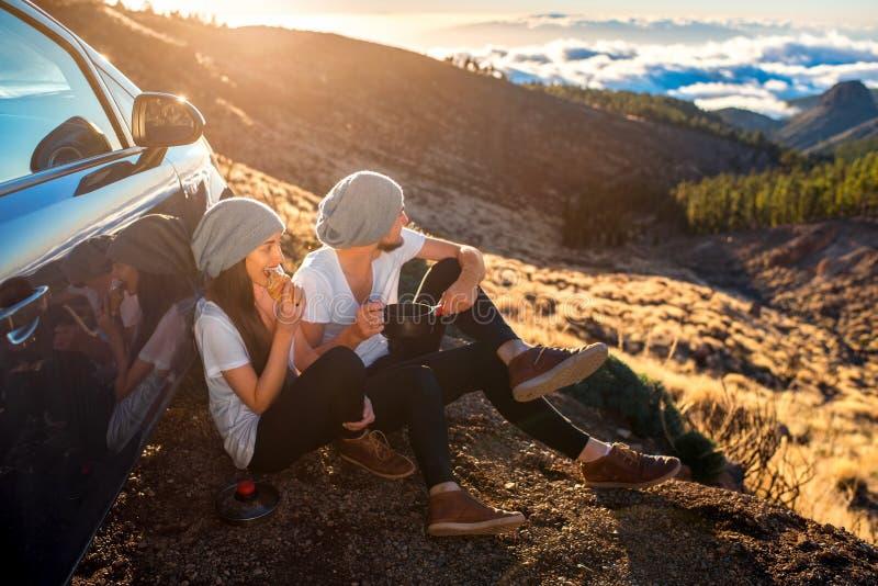 Coppie che hanno picnic vicino all'automobile fotografia stock libera da diritti