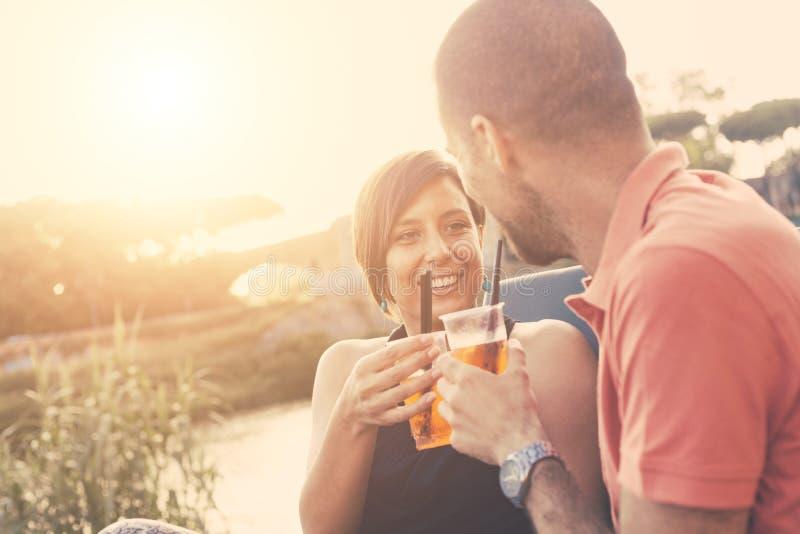 Coppie che hanno un cocktail all'aperto al tramonto fotografia stock libera da diritti