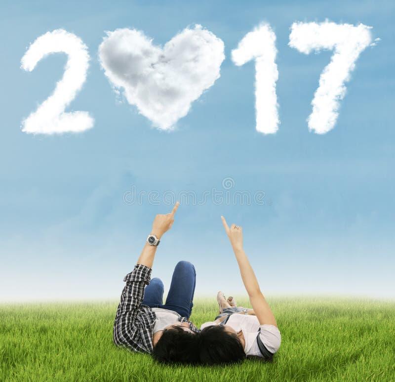 Coppie che indicano numero 2017 sul prato immagini stock libere da diritti