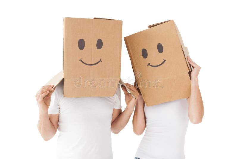 Coppie che indossano le scatole felici del fronte sopra le teste fotografia stock